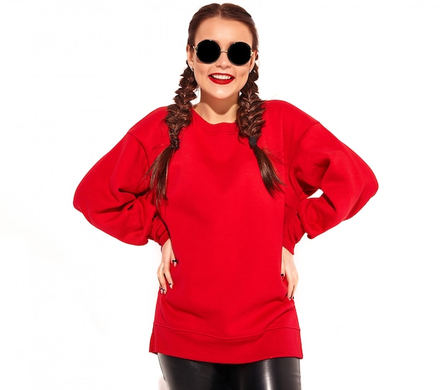 Portrait of young happy smiling woman model with bright makeup and colorful lips with two pigtails and sunglasses in summer red clothes isolated.