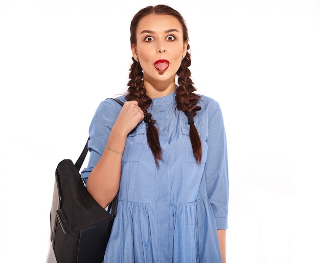 Portrait of young happy smiling woman model with bright makeup and red lips with two pigtails in hands in summer colorful blue dress and backpack isolated. showing her tongue