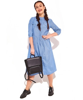 Portrait of young happy smiling woman model with bright makeup and red lips with two pigtails in hands in summer colorful blue dress and backpack isolated.