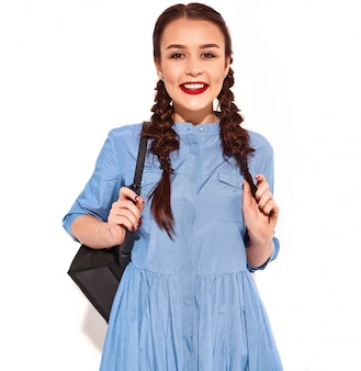 Portrait of young happy smiling woman model with bright makeup and red lips with two pigtails in hands in summer colorful blue dress and backpack isolated