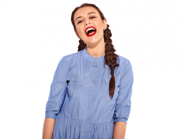 Portrait of young happy smiling woman model with bright makeup and red lips with two pigtails in hands in summer colorful blue dress isolated