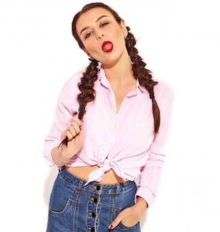 Portrait of young happy smiling woman model with bright makeup and red lips with two pigtails  in summer colorful pink tied shirt isolated, showing her tongue