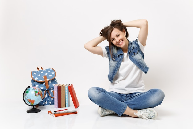 Portrait of young happy smiling woman student in denim clothes holding hair sitting near globe backpack, school books isolated