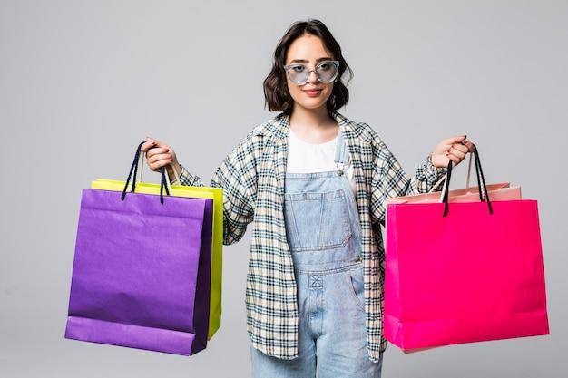 Ritratto di giovane donna sorridente felice in occhiali da sole con borse della spesa isolato su grigio. concetto di vendita.