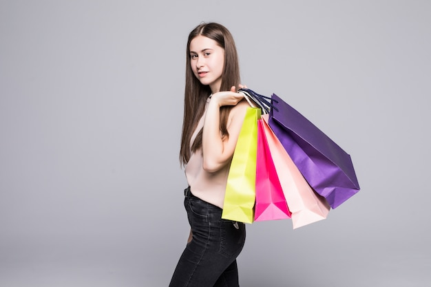 Portrait of young happy smiling woman with shopping bags over white wall