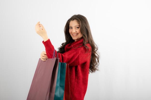 Ritratto di giovane donna sorridente felice con i sacchetti della spesa.