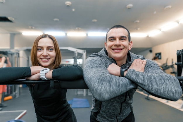 Portrait of young happy sporty couple, man and woman smiling
