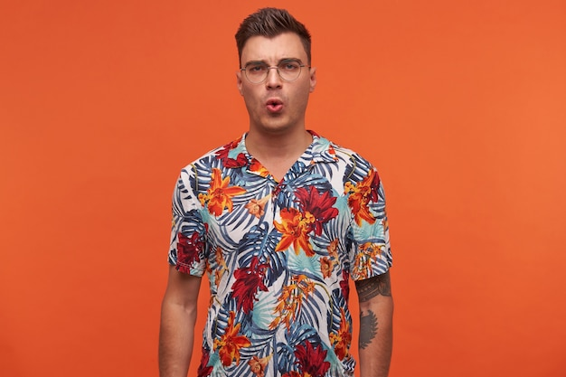 Portrait of young happy surprised man in flowered shirt, looks wondered, stands over orange background with copy space with wide open mouth.
