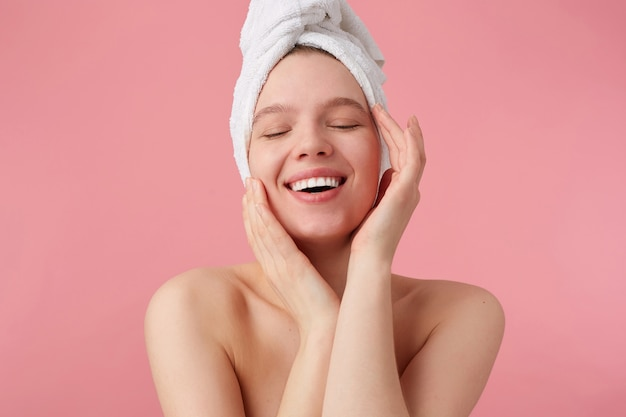 Portrait of young happy woman after shower with a towel on her head, broadly smiles with closed eyes, touches his face and smooth skin, stands