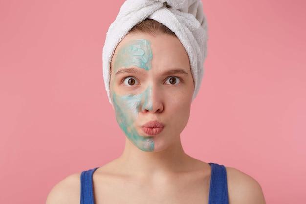 Ritratto di giovane donna felice dopo la doccia con un asciugamano in testa, con mezza maschera, sguardo sorpreso.