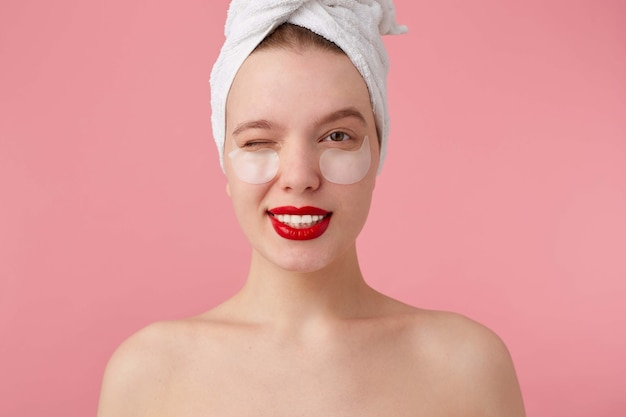Portrait of young happy woman after shower with a towel on her head, with patches and red lips, looking and winking.