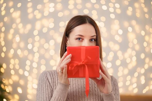 Ritratto di giovane donna felice labbra rosse che si nascondono dietro il contenitore di regalo avvolto.