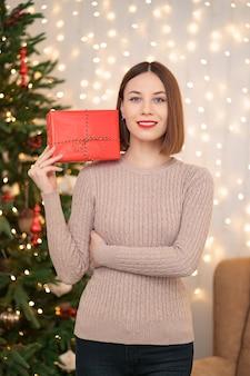 Ritratto di giovane donna felice labbra rosse che guarda l'obbiettivo che tiene una confezione regalo avvolta