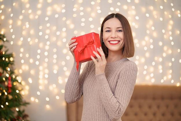 Ritratto di giovane donna felice labbra rosse guardando confezione regalo avvolto.
