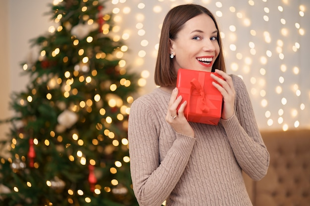 Ritratto di labbra rosse di giovane donna felice in posa con una confezione regalo avvolta.