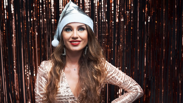 Portrait of young happy woman in silver santa hat and elegant dress.