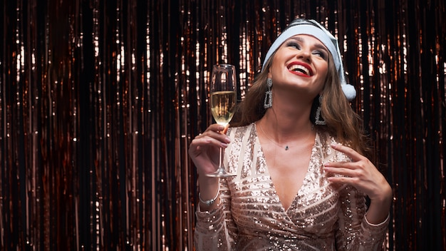 Portrait of young happy woman in silver santa hat with champagne glass in hands.