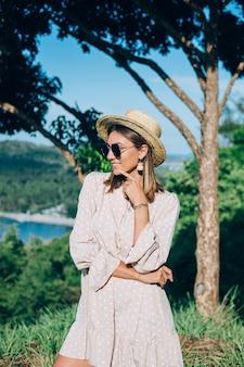 Ritratto di giovane donna felice in abito estivo, occhiali da sole e cappello di paglia