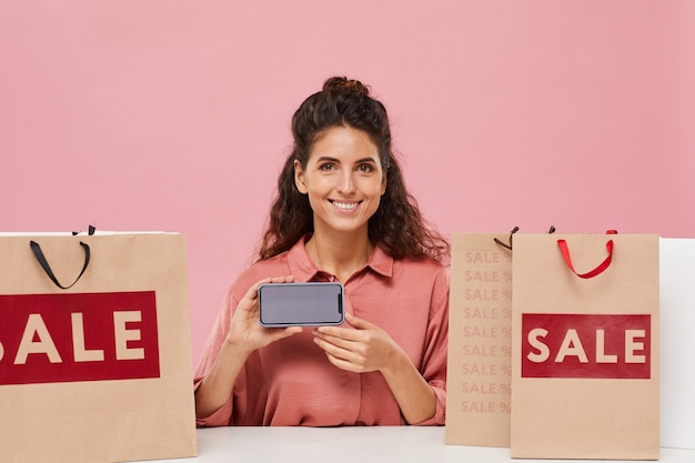 Portrait of young happy woman with curly hair smiling and showing the screen of her mobile phone she doing shopping online