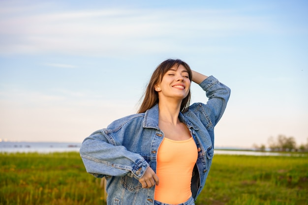 Portrait of a young happy woman with long hair, in jeans on a background of the sky dancing