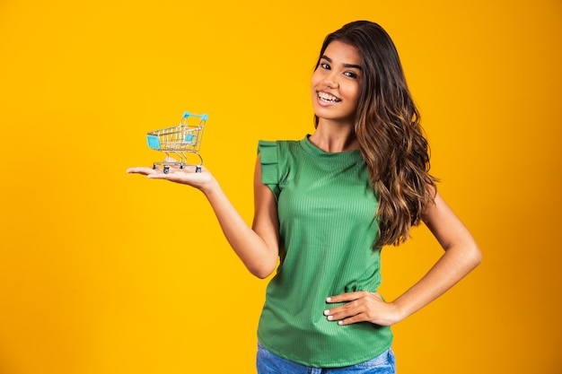 Portrait of young happy woman with shopping basket on yellow background