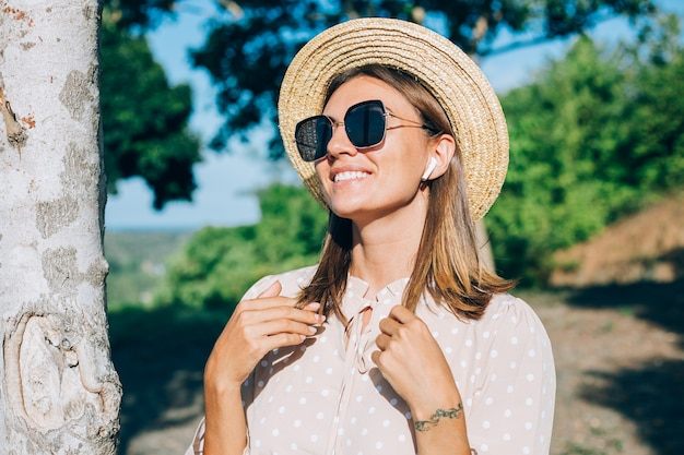 Portrait of young happy woman with sunglasses and straw hat