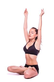 Ritratto di una giovane donna in buona salute facendo esercizi di yoga, isolato su sfondo bianco