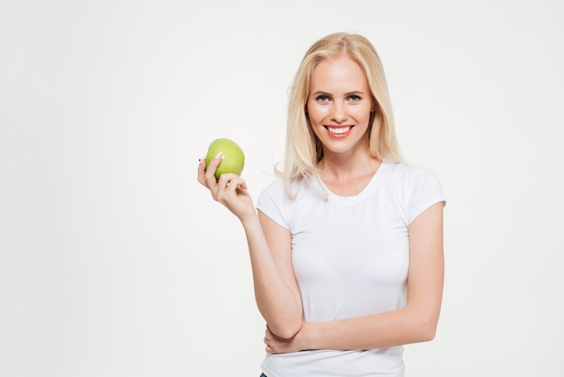 Portrait of a young healthy woman holding green apple