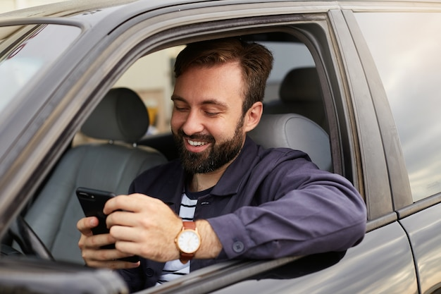 Portrait of young hendsome successful bearded man in a blue jacket and striped t-shirt, sits behind the wheel of the car, chatting with colleague by phone