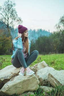 Portrait of young hipster girl enjoying an amazing view of mountains, pretty female traveler looking at the sky, sitting on large stones