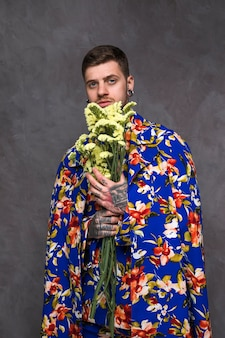 Portrait of a young hipster man with pierced ears and nose holding limonium flower in hand