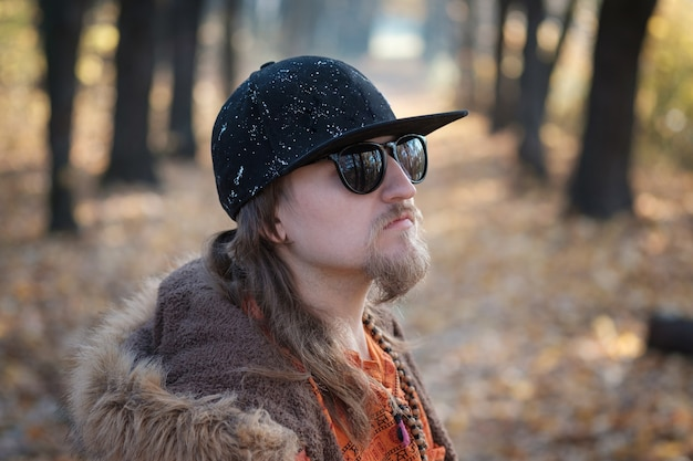 Portrait of a young hipster musician in black glasses and a black baseball cap in the autumn park with yellow foliage