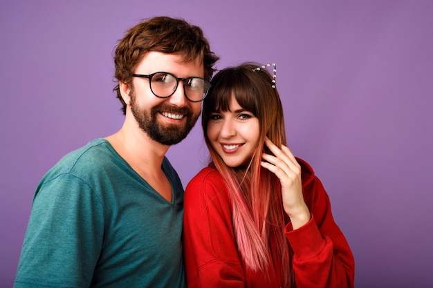 Portrait of young hipster pretty family couple hugs, wearing trendy casual outfits, boyfriends and girlfriends, relation goals, violet wall
