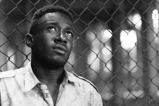 Portrait of young homeless african man against chain link fence in the streets outdoors in black and white