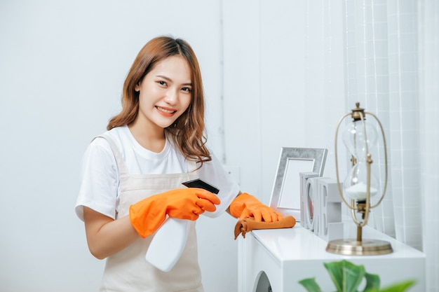 Portrait young housekeeper woman wearing apron and rubber gloves use cleaning solution in a spray bottle on white furniture and use a cloth to clean it