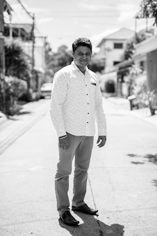 Portrait of young indian businessman in the streets outdoors in black and white
