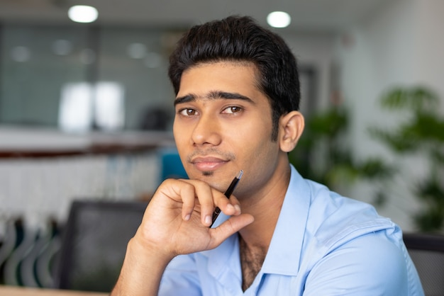 Portrait of young indian businessman or student sitting with pen