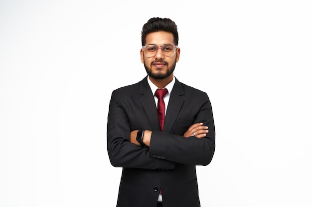 Portrait of young indian businessman with crossed arms on white isolated background.