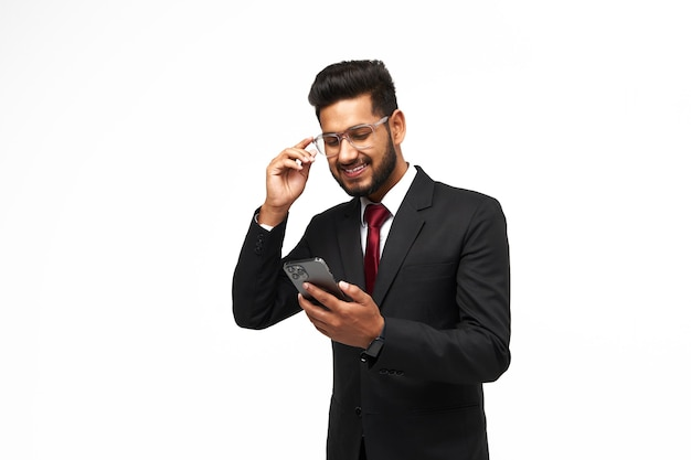 Portrait of young indian manager using his phone on white isolated background