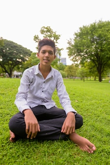 Portrait of young indian teenage boy relaxing at the park