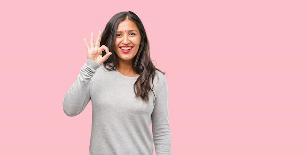 Portrait of young indian woman cheerful and confident doing ok gesture, excited and screaming, concept of approval and success