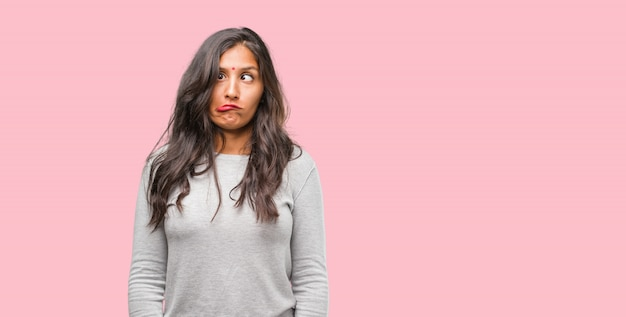 Portrait of young indian woman crazy and desperate, screaming out of control