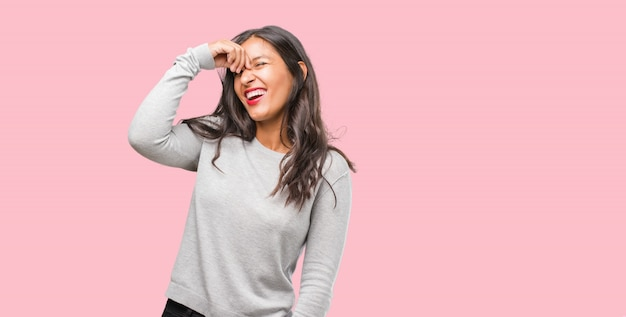 Portrait of young indian woman laughing and having fun, being relaxed and cheerful, feels confident and successful