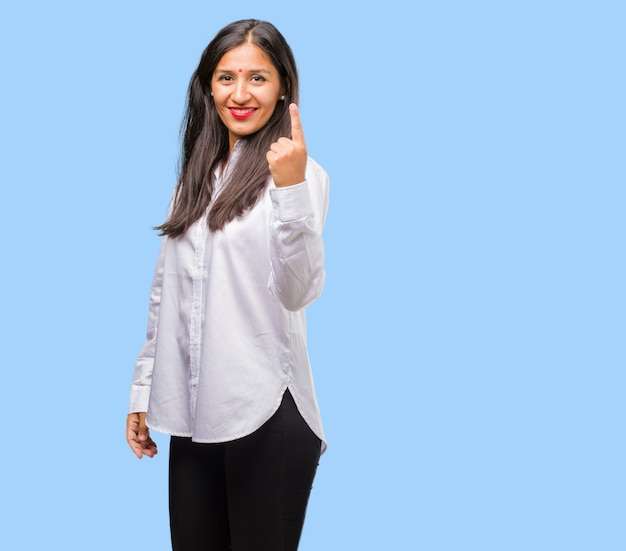 Portrait of a young indian woman showing number one, symbol of counting, concept of mathem