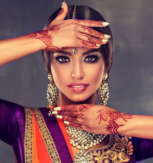 Portrait of young indian woman with mehndi henna tattoos on the hands and bright makeup