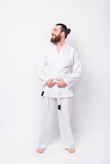 Portrait of young instructor man wearing taekwondo uniform smiling and looking aside