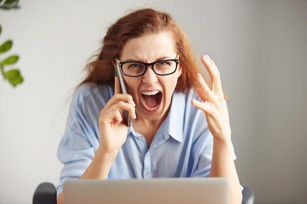 Ritratto di una giovane imprenditrice irritata con gli occhiali e la camicia guardando con rabbia