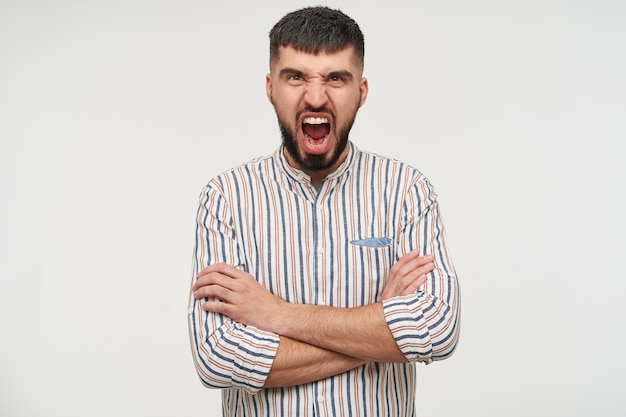 Portrait of young irritated dark haired bearded man keeping his mouth wide opened while screaming and crossing his hands on chest, isolated over white wall