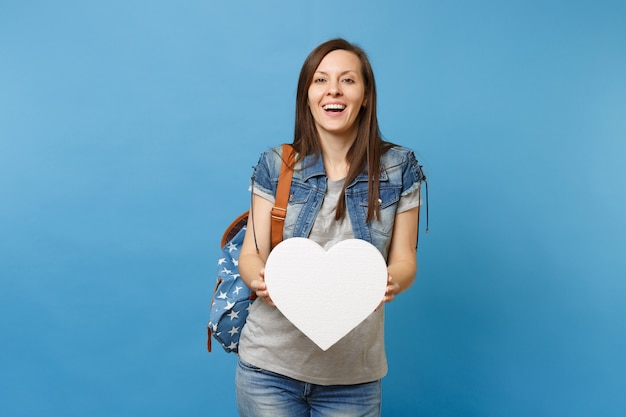 Portrait of young joyful beautiful woman student in denim clothes with backpack holding white heart with copy space isolated on blue background. education in high school. copy space for advertisement.
