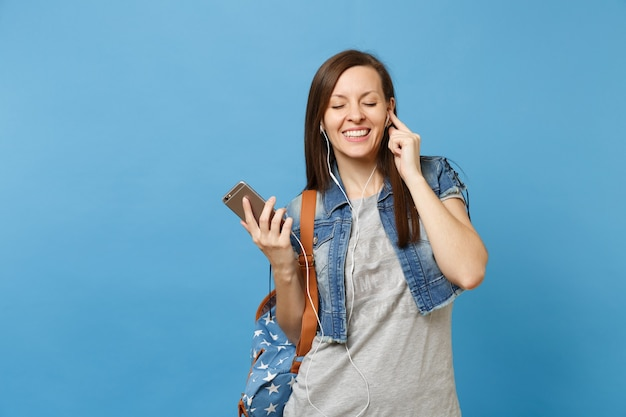 Portrait of young joyful beautiful woman student with backpack and earphones listening music holding mobile phone isolated on blue background. education in high school. copy space for advertisement.